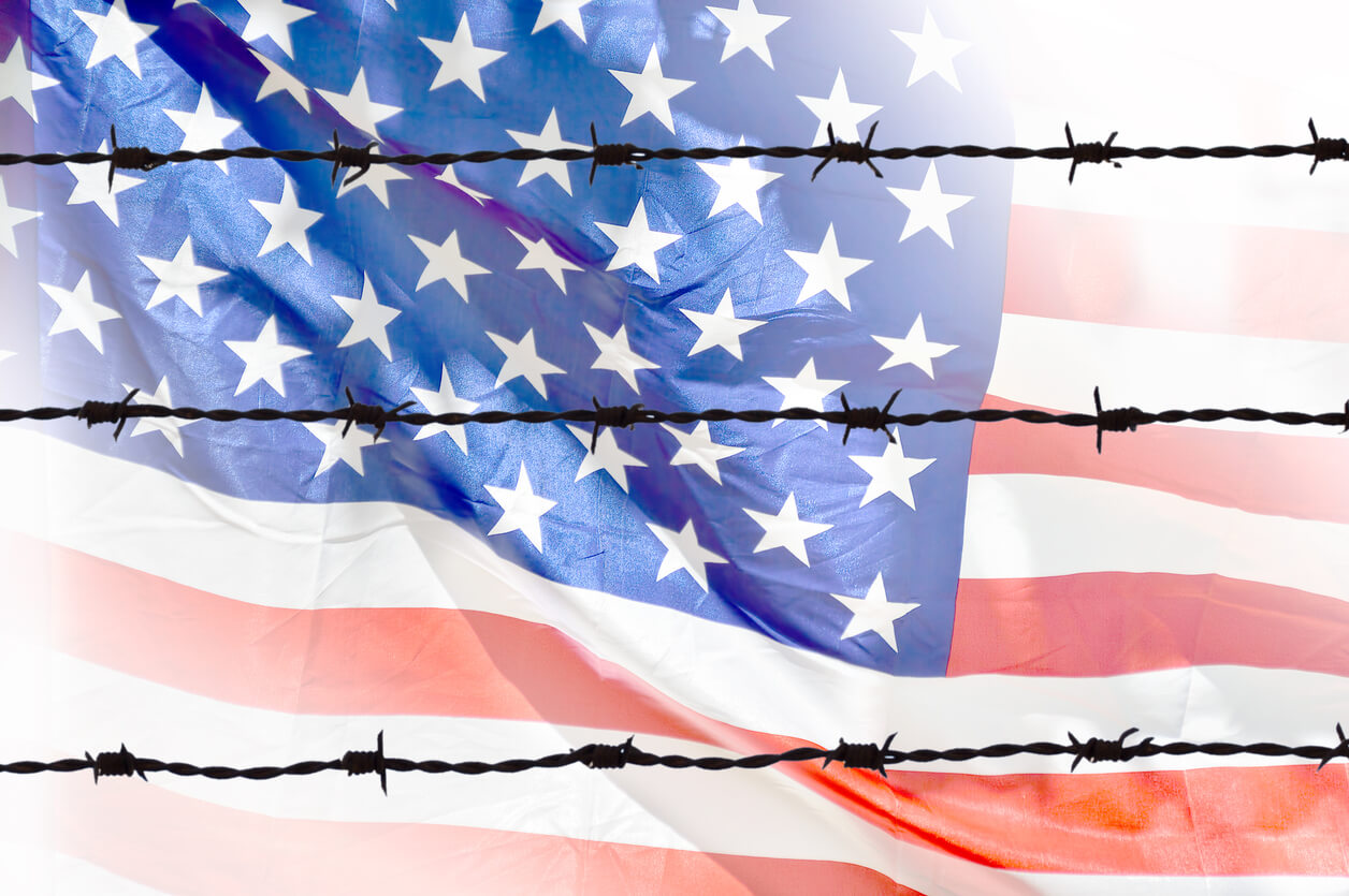 u.s flag behind barbed wire